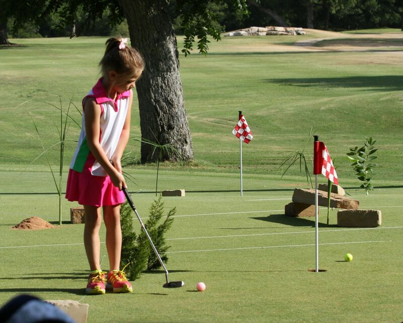 A young golfer practices her short game